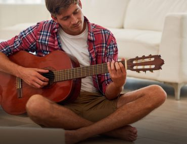 A man learning to play the guitar with online music classes in Dubai