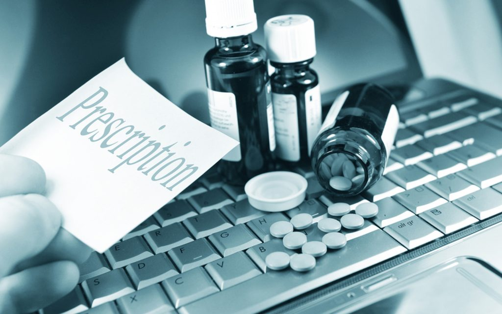 Prescription and medications over a laptop