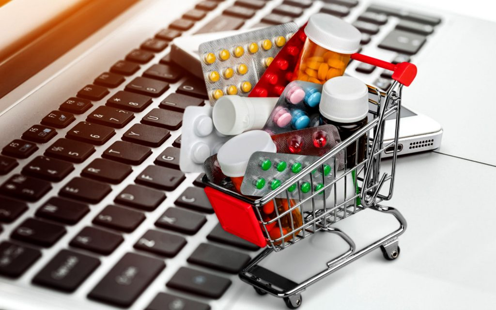Miniature shopping trolley with medications with a laptop and a phone in the background