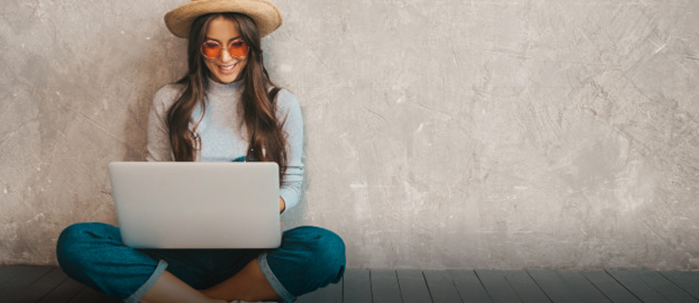 Woman smiling at a laptop screen sitting with her legs crossed