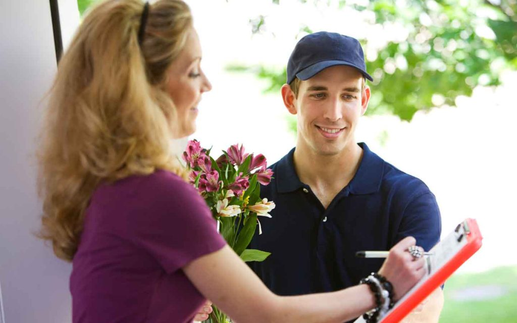 Woman singing delivery from on doorstep with a flower bouquet in hand