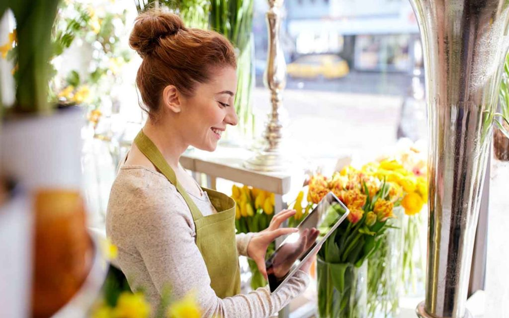 Female florist in apron in a flower shop checking online order on an iPad