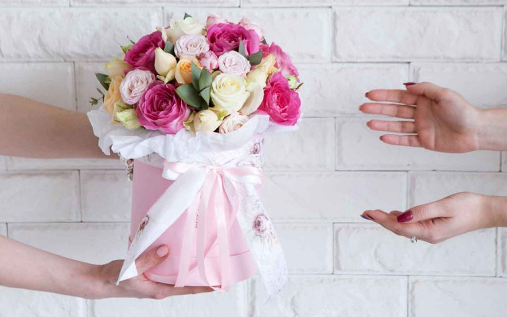 Shot of hands giving and receiving a  beautiful floral arrangement