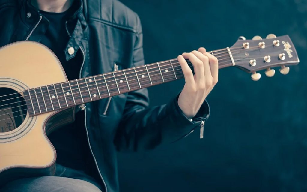 Man in a leather jacket playing a guitar with online guitar classes
