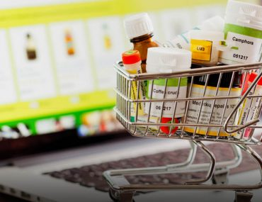 shopping cart with medication placed over a laptop