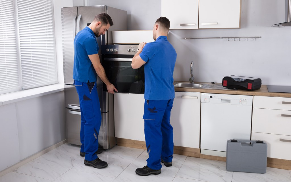 Handymen installing appliances, from cheap movers and packers Dubai
