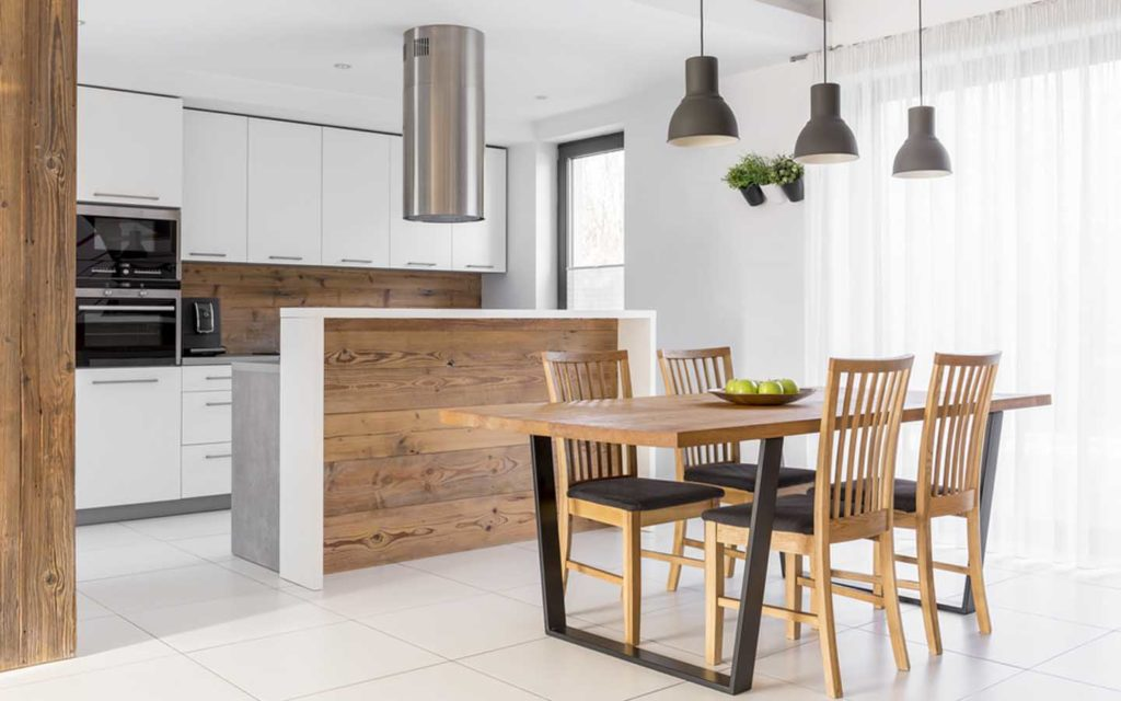 A brand new kitchen with a set of chairs and table and other accessories visible.