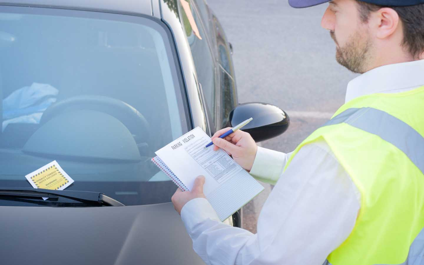 An officer writing a ticket, which one can confirm on check fines in Dubai websites