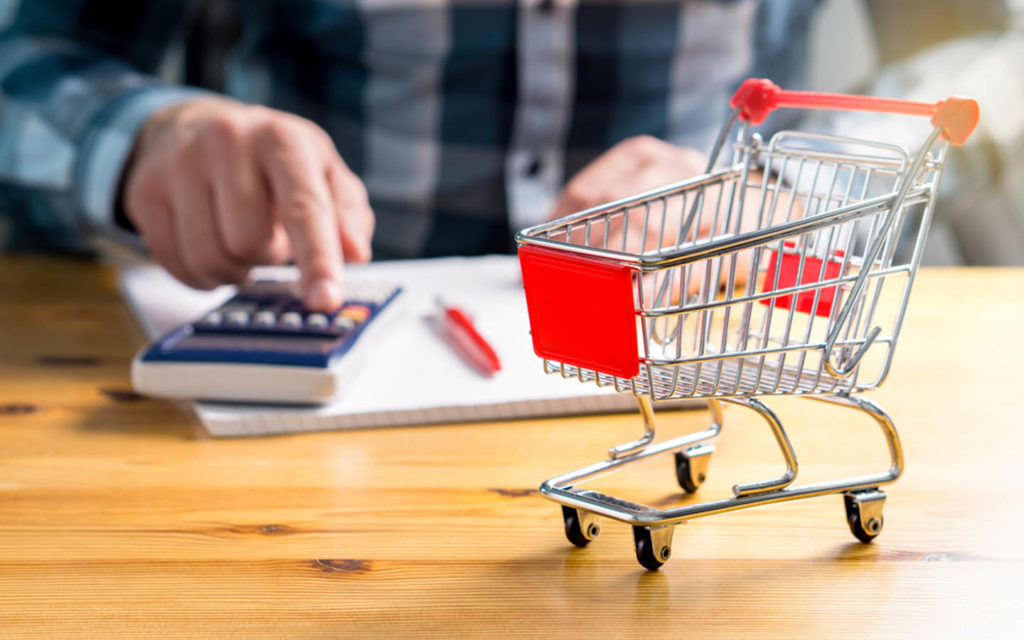 Person calculating cost with small grocery cart on table