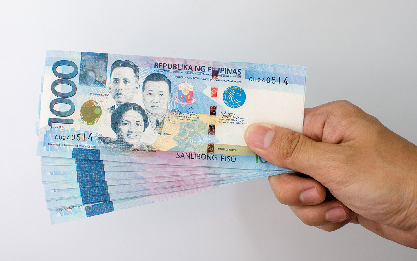 Hand holding a stack of PHP 1000 notes