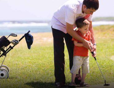 Adult training kid to golf