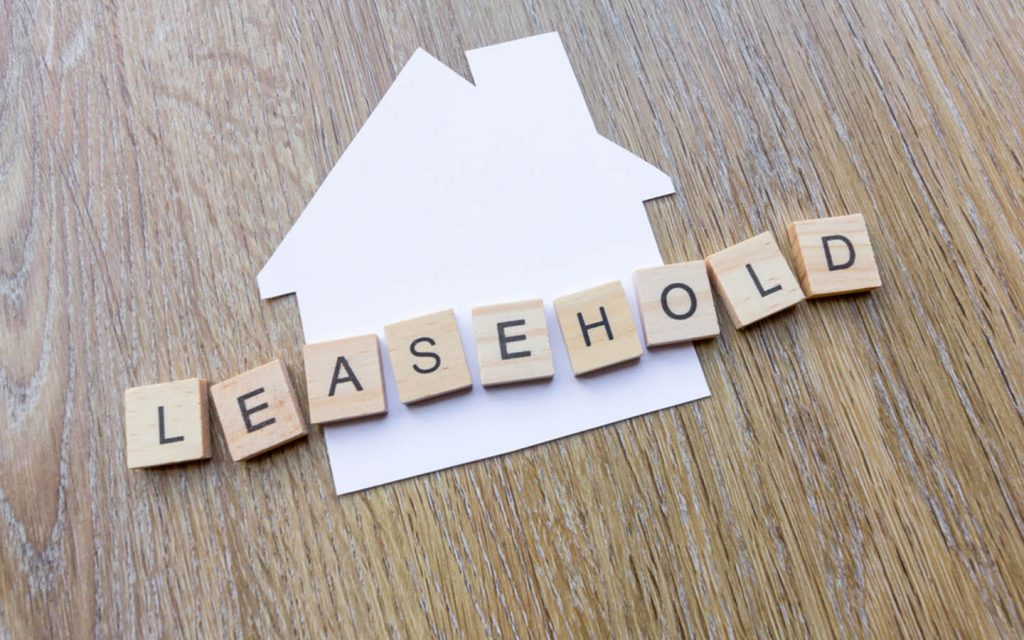 Spelling of leasehold presented in wooden blocks on top of paper cutout of house