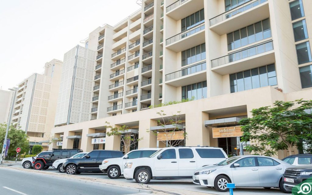 Cars parked in front of apartment building in Al Raha Beach