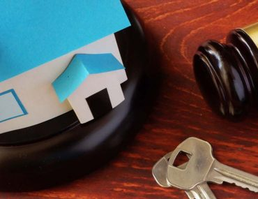 A gavel, key and a miniature home