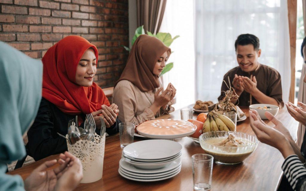 Muslim family reciting prayer for breaking the Ramadan fast during Iftar