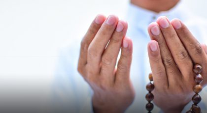 Man holding hands up in prayer with prayer beads in hand