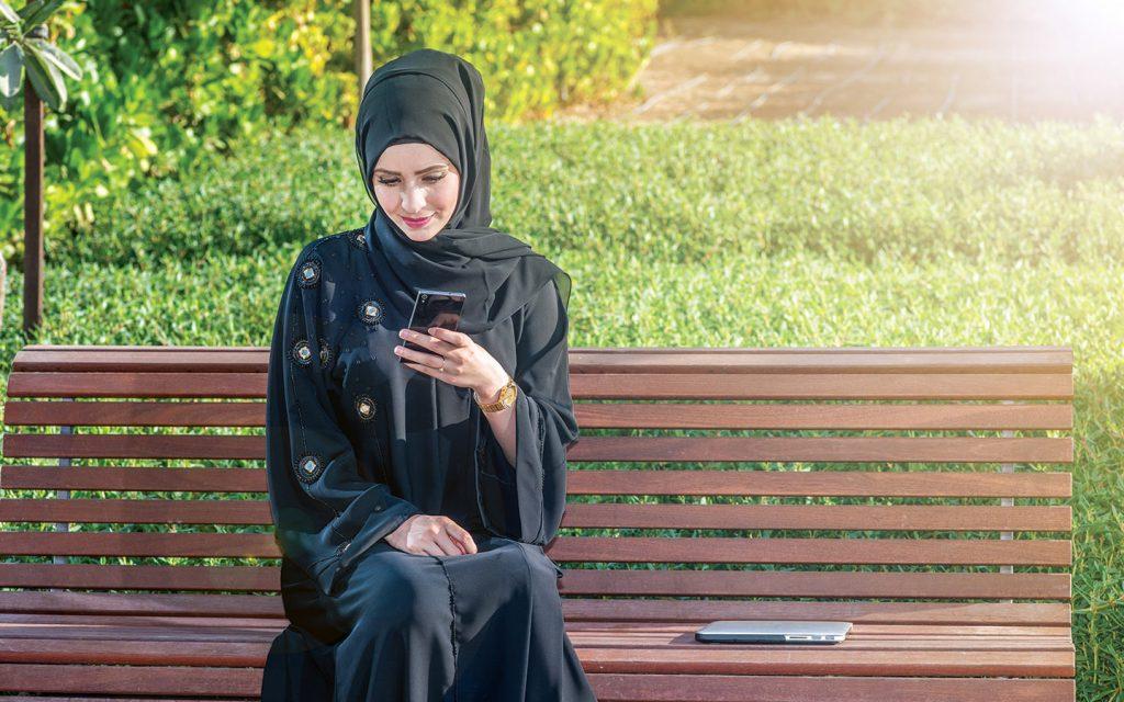 امرأة تتصفح الأخبار عبر هاتفها