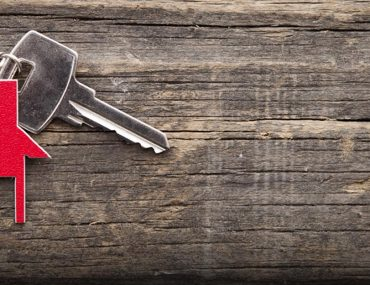 red house keychain on a wooden background