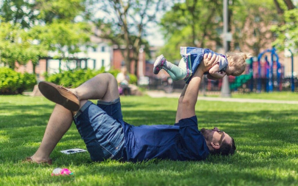 A father playing with her daughter in a park