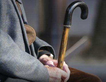 Elderly man sitting with cane in hand