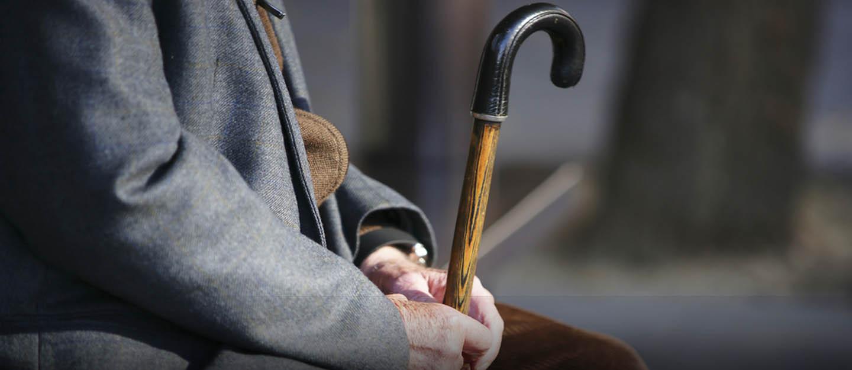 Elderly man sitting with cane in hand