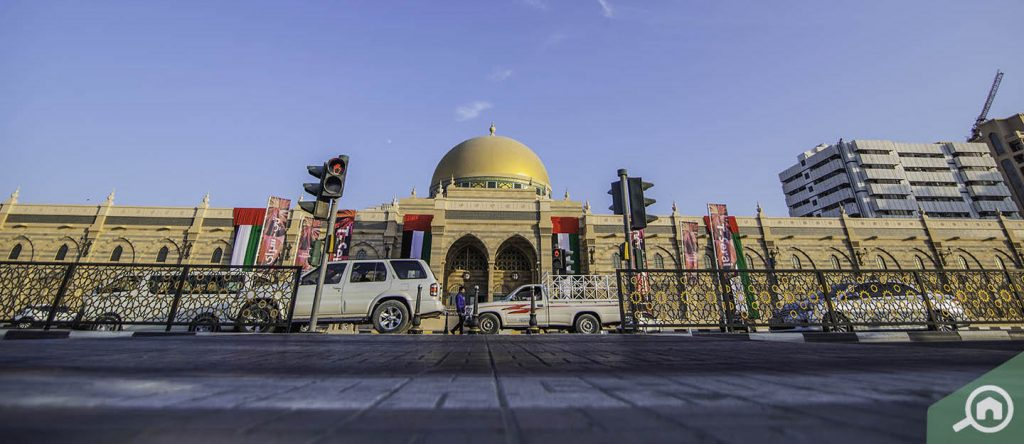 Sharjah Islamic Museum Facade with cars parked nearby