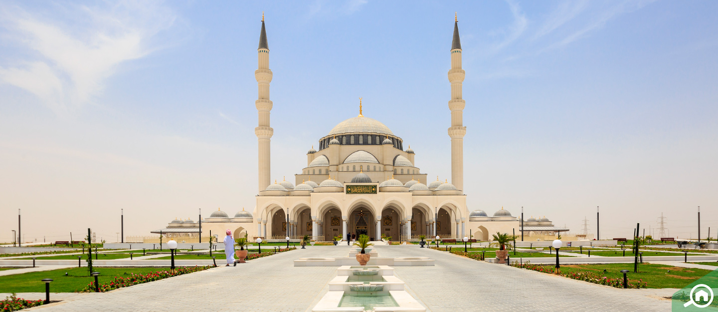 Exterior view of the new Sharjah Mosque with fountains and grounds