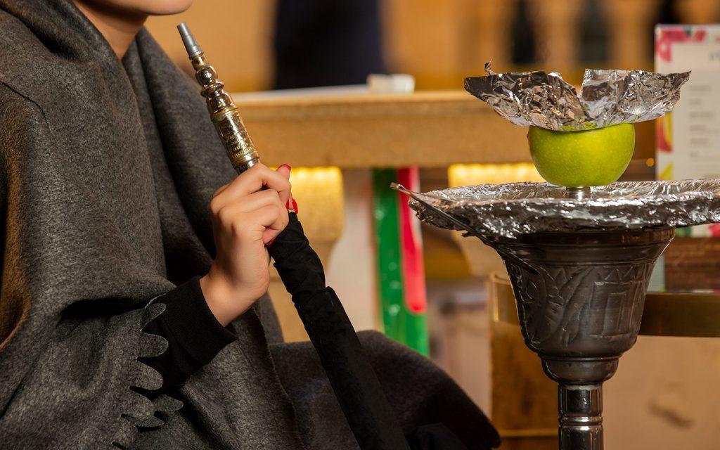 فتاة تدخن الشيشة