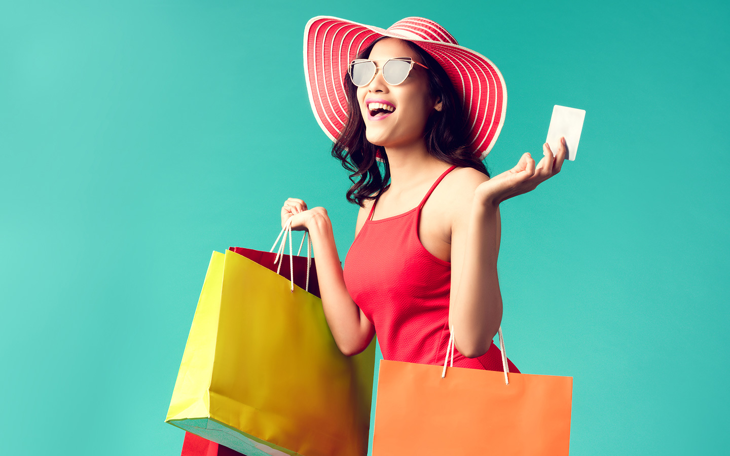 Happy woman holding credit card and shopping bags, going to one of the events in Dubai August 2019