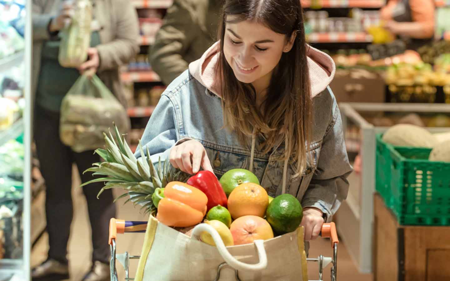 Woman grocery shopping with a bag full of vegetables and fruits