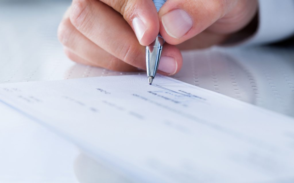person signing a cheque for short-term rental contract in Dubai