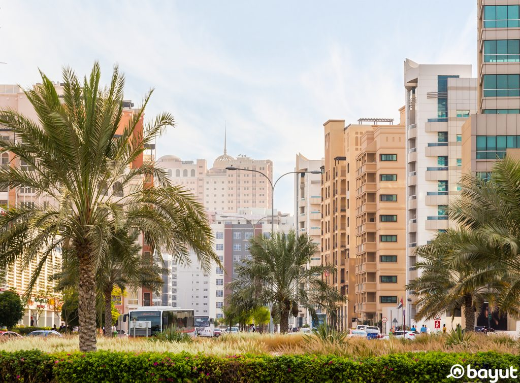 Residential and office buildings in Dubai Silicon Oasis with nearby palms and landscaping on a bright sunny day