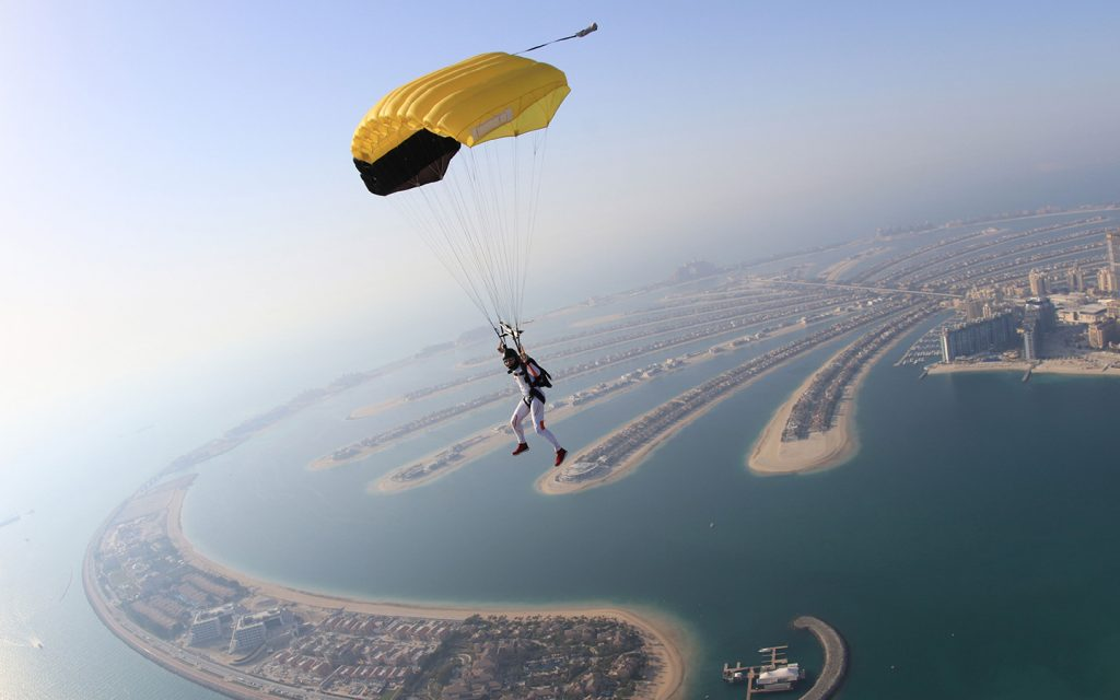 view of a man skydiving over Palm Jumeirah in Dubai