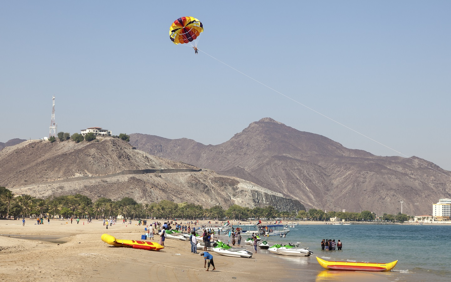 Boats on the shore of Khorfakkan Beach and parasailing activity