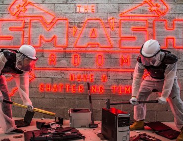 Two men are smashing things at the Smash Room
