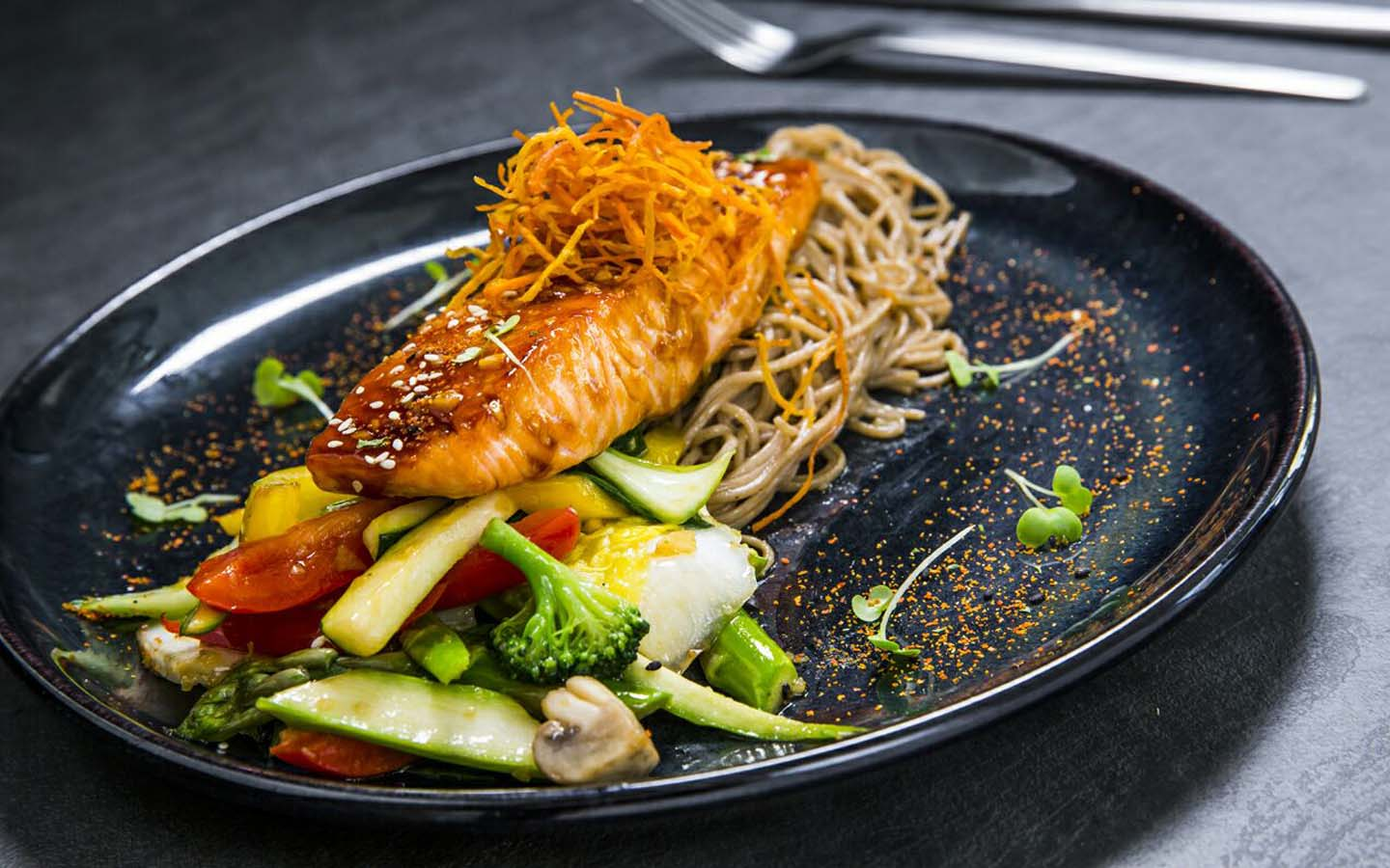 Fried fish with vegetables and noodles.