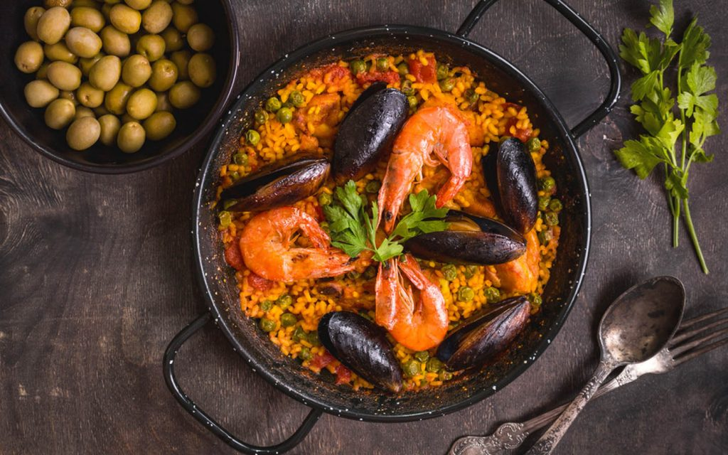 Paella in a black pan with shrimps, rice and mussels