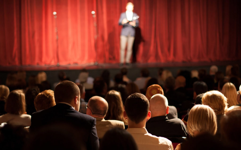 A stand-up comedy show with audience and comedian on stage