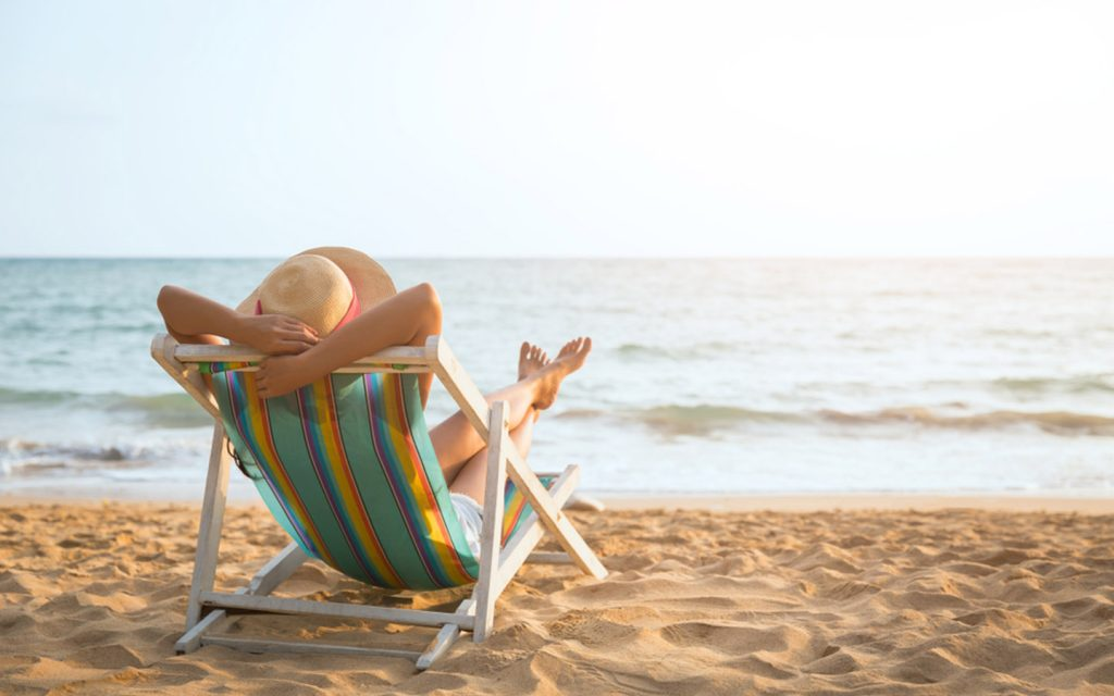 Person relaxing on a sun bed at a private beach during a staycation in Abu Dhabi 2020