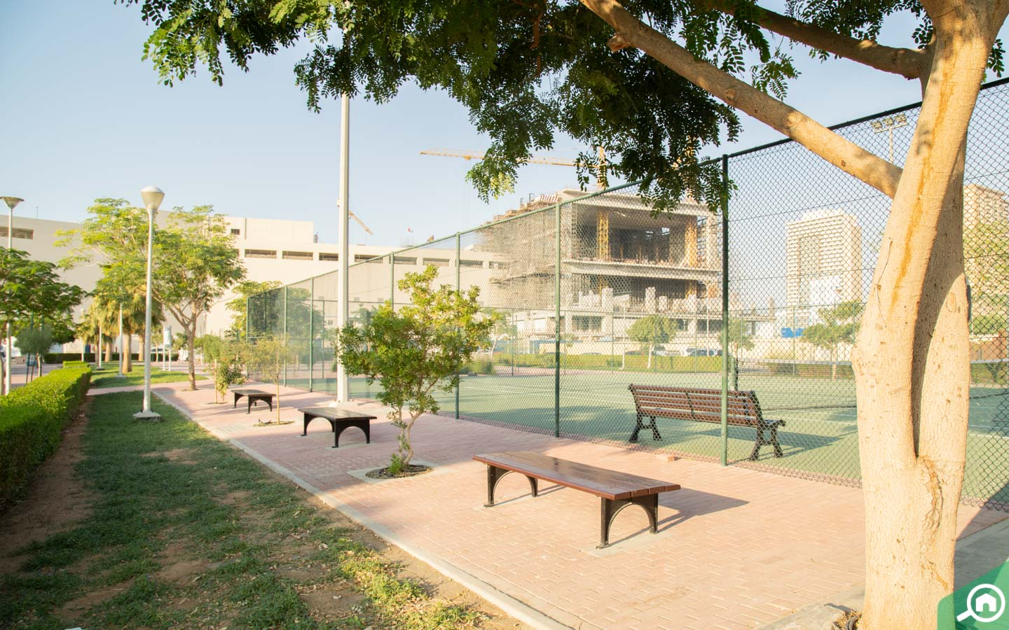 View of benches, greenery and Jumeirah Village triangle tennis court