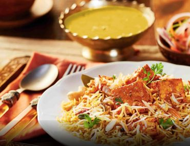 Best biryani in Ajman with traditional sauces and salad