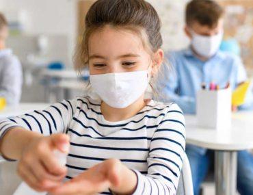 Kid using hand sanitiser in class