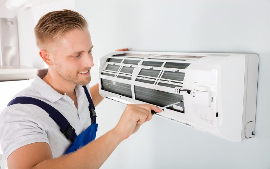 A man cleaning AC filters to help save up on energy bills in Dubai