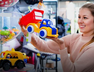 A woman choosing between different types of toy trucks