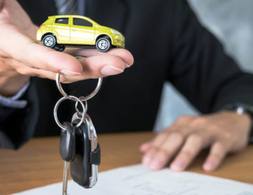 Person handing over car keys and a model car