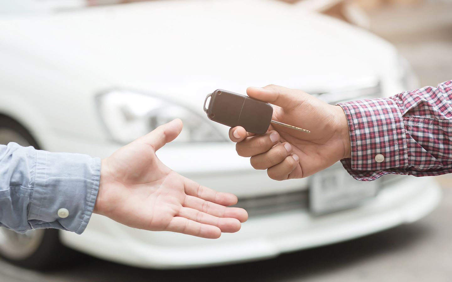 Two hands exchanging car keys