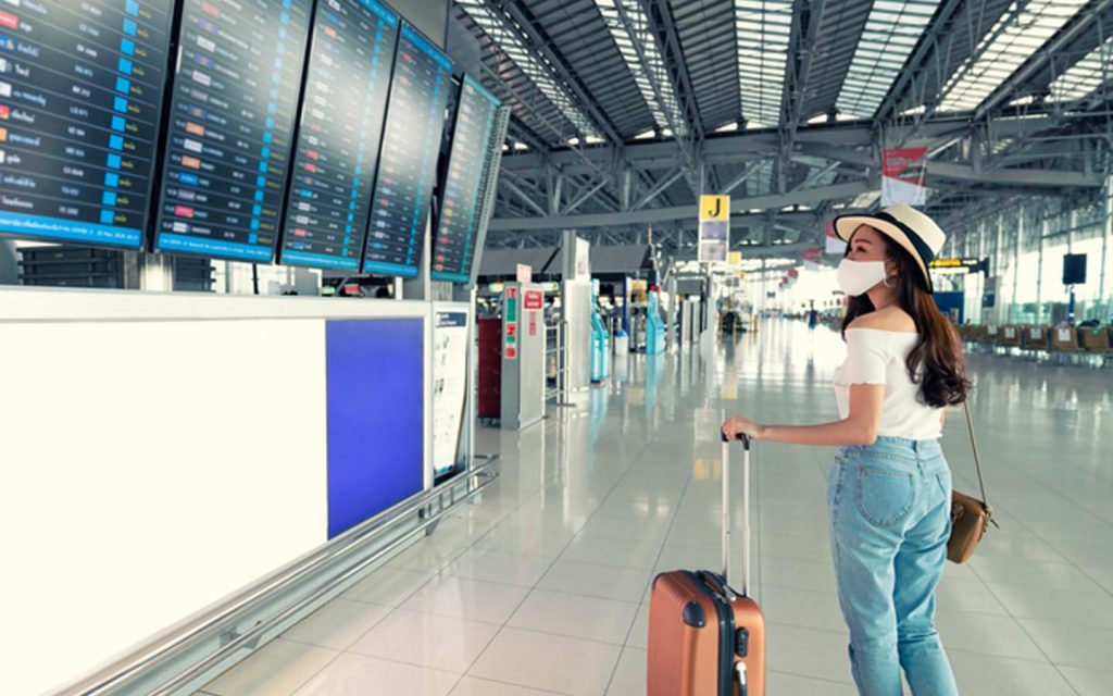 Female traveller with mask looking at airport schedule board