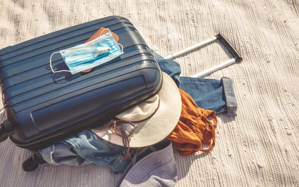 Suitcase with surgical mask on top and items spilling out
