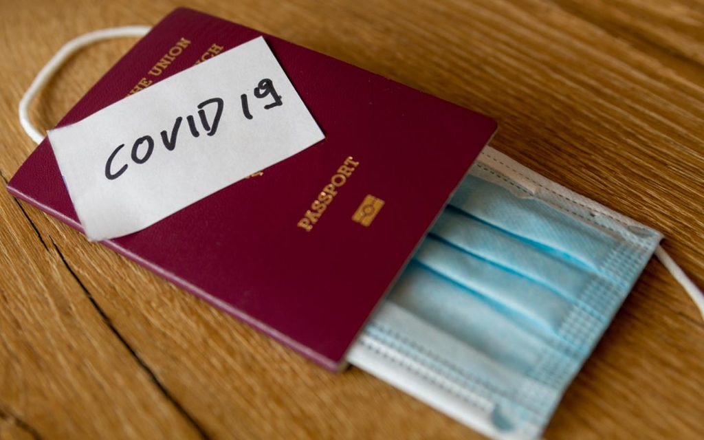 Surgical mask inside passport with Covid 19 written on top