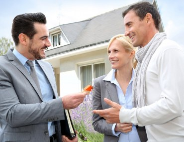 A Dubai broker handing the key to the house of a young happy couple